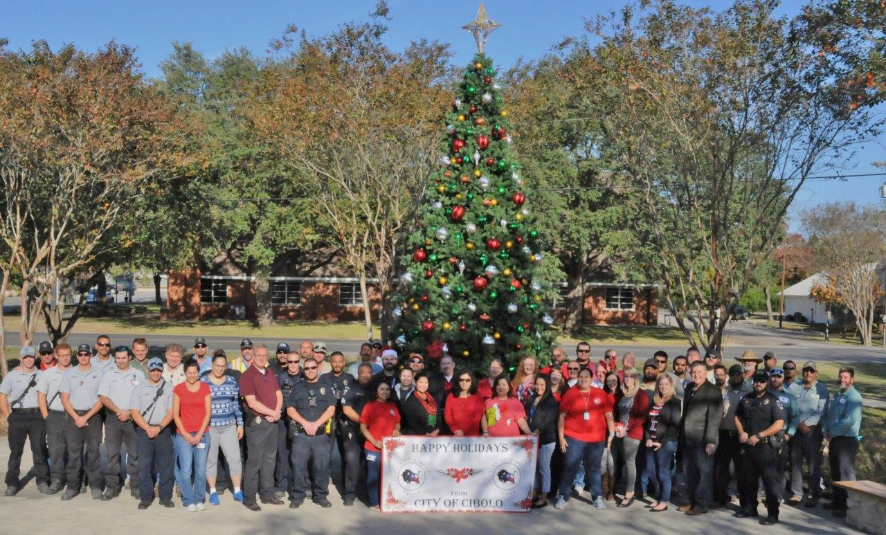 A group picture of city staff in front of a Christmas Tree